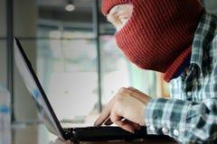 穿巴拉克拉法帽的被掩没的黑客使用窃取重要信息数据的膝上型计算机 互联网安全和保密性罪行概念 S 免版税库存图片