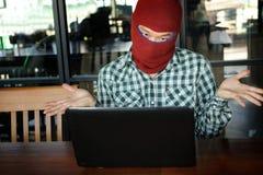 穿巴拉克拉法帽的被掩没的黑客看膝上型计算机在窃取重要信息数据以后 互联网罪行概念 库存照片
