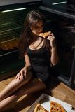 穿庄重装束的性感的妇女坐地板和吃薄饼 免版税库存图片