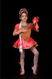 穿当地俄国服装的逗人喜爱的小女孩隔绝在黑背景 她是跳舞和拿着俄式三弦琴在手上 图库摄影