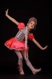 穿当地俄国服装的逗人喜爱的小女孩隔绝在黑背景 她跳舞 免版税库存图片