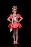 穿当地俄国服装的逗人喜爱的小女孩隔绝在黑背景 她跳舞 免版税库存照片