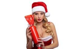 穿性感的圣诞节服装的华美的白肤金发的女性摆在与 免版税图库摄影