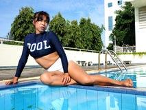 穿性感的泳装的妇女坐在水池的边缘 免版税图库摄影