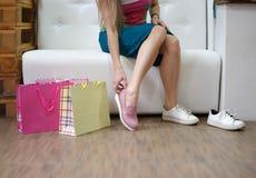 穿戴一个对在商店背景的浅粉红色的起动的一个少妇 选择鞋子的迷人的女孩在商店 库存图片