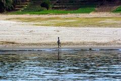 穿戴了简而言之和衬衣走沿在一含沙Ã ¡ rea的河岸的埃及人 免版税库存照片