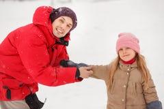 穿戴他的女儿手套的愉快的父亲的图片在冬天公园 免版税图库摄影