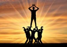 穿戴冠的一个自私和自恋的人的剪影,他在人人群站立  免版税图库摄影