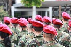 穿戴在伪装战士,男孩和女孩有红色桶的在一条军事线 库存照片