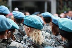 穿戴在伪装战士,男孩和女孩有红色桶的在一条军事线 库存图片