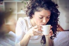穿戴女孩褂子早晨白色的咖啡杯 15个妇女年轻人 免版税库存照片