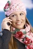 穿戴的女孩移动俏丽微笑使用温暖 免版税库存照片