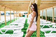 穿戴的放松的美丽的少妇在游泳池附近的轻便马车休息室 库存图片