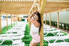 穿戴的放松的美丽的少妇在游泳池附近的轻便马车休息室 库存照片