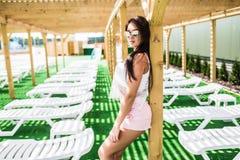 穿戴的放松的美丽的少妇在游泳池附近的轻便马车休息室 图库摄影
