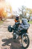 穿摩托车服装,防护服装,设备,有旁边袋子的冒险旅游摩托车的骑自行车的人女孩 ?? 库存图片