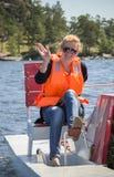 穿救生衣的女孩,当在小船旅行时 免版税库存照片