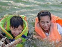 穿救生衣的母亲和儿子安全地游泳和享用 免版税库存图片