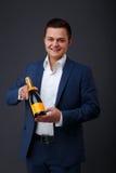 穿无尾礼服的绅士拿着香槟瓶 免版税库存图片