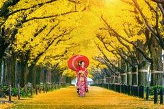 穿日本传统和服的美丽的女孩在黄色银杏树树行在秋天 秋天公园在东京,日本 免版税库存照片