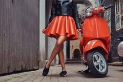 穿时髦的红色裙子和皮夹克的性感的妇女站立在有两经典意大利语的一条老狭窄的街道上 免版税库存照片