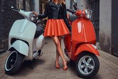 穿时髦的红色裙子和皮夹克的性感的妇女站立在有两经典意大利语的一条老狭窄的街道上 免版税库存图片