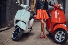 穿时髦的红色裙子和皮夹克的性感的妇女站立在有两经典意大利语的一条老狭窄的街道上 库存照片