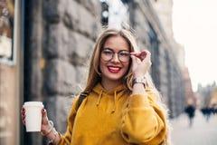 穿明亮的黄色运动衫的年轻时髦的女学生 被启发的少妇笑和感人的glasse特写镜头画象  库存照片