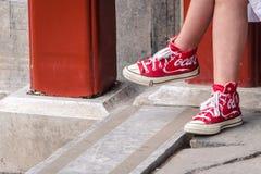 穿有可口可乐商标的女孩红色鞋子对此 库存照片