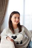 穿有微笑在照相机的逗人喜爱的绵羊和偶然牛仔裤的图象的年轻美丽的女孩画象滑稽的毛线衣 免版税图库摄影