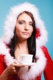 穿有杯子的画象妇女圣诞老人服装在蓝色的热的饮料 免版税图库摄影
