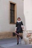 穿有白色小点的端庄的妇女一件黑葡萄酒礼服 免版税库存照片