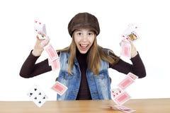 穿有盖帽的快乐的女孩布朗高领衫和牛仔布背心在她的在白色背景的头玩杂耍的纸牌 免版税库存图片