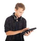 一个逗人喜爱的十几岁的男孩的画象有耳机和片剂计算机的。 免版税库存照片
