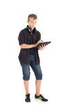 一个逗人喜爱的十几岁的男孩的画象有耳机和片剂计算机的。 库存照片