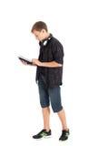 一个逗人喜爱的十几岁的男孩的画象有耳机和片剂计算机的。 免版税库存图片