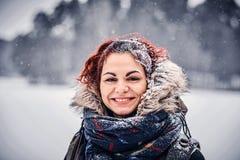 穿有背包的一个美丽的红头发人女孩的画象温暖的衣物站立在冬天森林附近 图库摄影