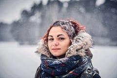 穿有背包的一个美丽的红头发人女孩的画象温暖的衣物站立在冬天森林附近 免版税库存照片