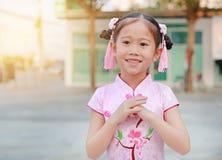 穿有问候姿态庆祝的愉快的矮小的亚裔儿童女孩桃红色传统中国礼服的农历新年 免版税库存照片