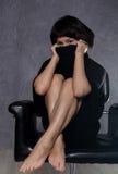 穿有高衣领的,在扶手椅子的姿势的美丽的时兴的夫人一件哥特式黑礼服 库存图片