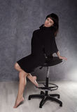 穿有高衣领的,在扶手椅子的姿势的美丽的时兴的夫人一件哥特式黑礼服 免版税图库摄影