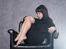穿有高衣领的,在白色烟的姿势的美丽的时兴的夫人一件哥特式黑礼服在一把皮革扶手椅子 图库摄影