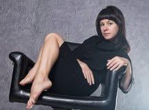 穿有高衣领的,在白色烟的姿势的美丽的时兴的夫人一件哥特式黑礼服在一把皮革扶手椅子 免版税图库摄影