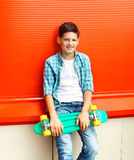 穿有滑板的时髦的微笑的少年男孩一件方格的衬衣 免版税库存图片