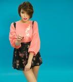 穿桃红色女衬衫和礼服的迷人的妇女 免版税库存照片