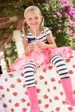 穿桃红色惠灵顿启动的女孩 免版税库存图片
