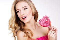 穿桃红色礼服用糖果的性感的女孩。 免版税库存照片