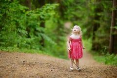 穿桃红色礼服的小女孩所有单独走 库存照片