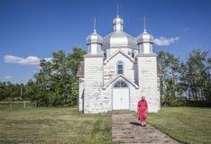 穿桃红色礼服的年长资深妇女离开教会 免版税库存照片