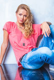 穿桃红色衬衣的白肤金发的少妇,当摆在为camer时 库存照片